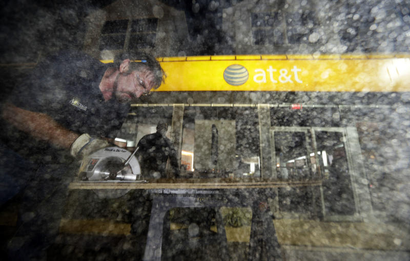 Sawdust flies in the air as Brian Rogers, left, cuts a board with a circular saw, as he and Dwayne Wallace board up an AT&T store in Rehoboth Beach, Del. on Saturday, Oct. 27, 2012 as Hurricane Sandy approaches the east coat. (AP Photo/Alex Brandon)
