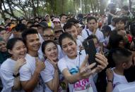 """Pannika Wanich, center, spokesperson of the anti-military Future Forward Party take selfies with supporters ahead of a run dubbed as """"Run Against Dictatorship"""" at a park in Bangkok, Thailand, Sunday, Jan. 12, 2020. About 6000 runners participated in a 3 kilometer run to demonstrate against the government led by former army general Prayuth Chan-ocha. (AP Photo/Gemunu Amarasinghe)"""