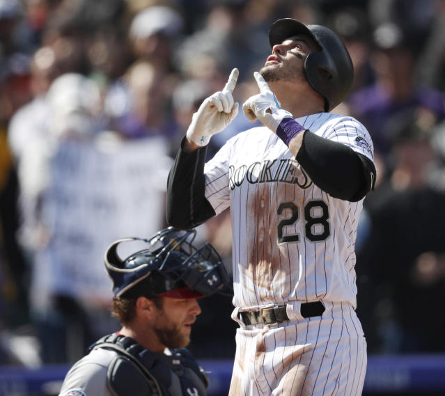 Colorado Rockies' Nolan Arenado gestures as he crosses home plate after hitting a two-run home run off Washington Nationals starting pitcher Erick Fedde in the first inning of a baseball game Sunday, Sept. 30, 2018, in Denver. (AP Photo/David Zalubowski)