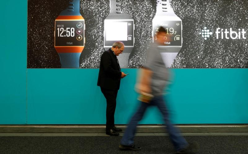 FILE PHOTO: Visitors walk past an advertising billboard for Fitbit Ionic watches at the IFA Electronics Show in Berlin