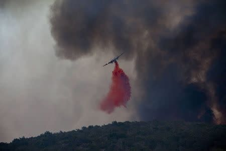 Firefighters battle a blaze in San Marcos, California May 14, 2014. REUTERS/Sam Hodgson