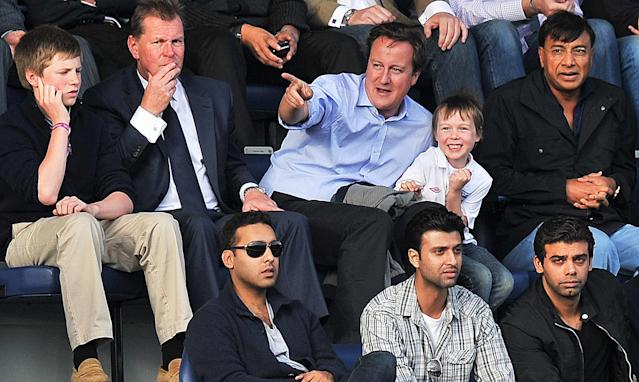 British Prime Minister David Cameron (C) and his son Arthur (C) react along with Indian Steel magnate Lakshmi Mittal (R) as Aston Villa score during a Premiership football match between QPR and Aston Villa at home to Queens Park Rangers at the Loftus rd Stadium, London on September 25, 2011. AFP PHOTO/Carl de Souza. RESTRICTED TO EDITORIAL USE. No use with unauthorized audio, video, data, fixture lists, club/league logos or 'live' services. Online in-match use limited to 45 images, no video emulation. No use in betting, games or single club/league/player publications. (Photo credit should read CARL DE SOUZA/AFP/Getty Images)
