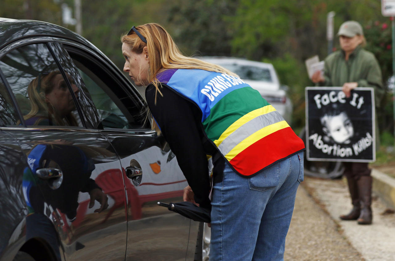 Clinic escort Kim Gibson speaks with driver as they attempt to enter the Jackson Women's Health Organization's clinic parking lot, the only facility in the state that performs abortions, Tuesday, March 20, 2018 in Jackson, Miss. A federal judge is temporarily blocking a new Mississippi law that bans abortion after 15 weeks, the most restrictive abortion law in the United States. (AP Photo/Rogelio V. Solis)