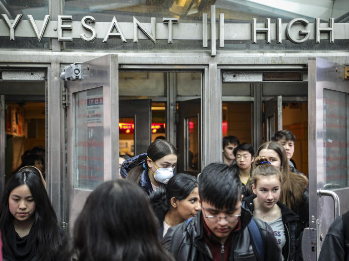 Students at Stuyvesant High School leave after classes end for the week, Friday, March 13, 2020, in New York. As concerns continue to grow around the spread of Covid-19, the city's Mayor Bill de Blasio has been reluctant to close the school system because of the consequences for students and families. (AP Photo/Bebeto Matthews)