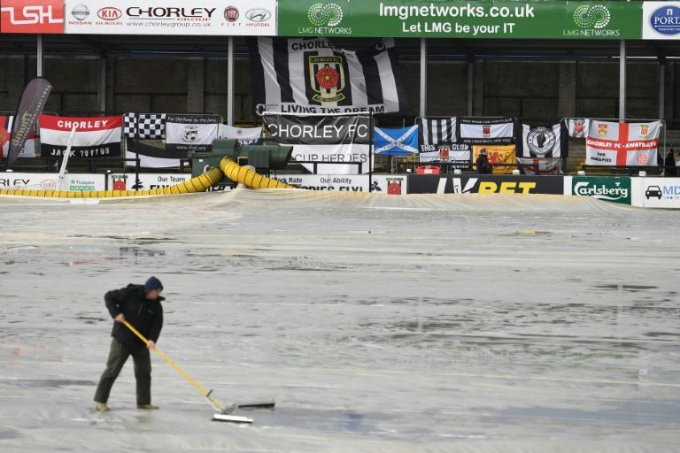 Groundstaff clear water off the covers at Victory Park stadium, the home of Chorley