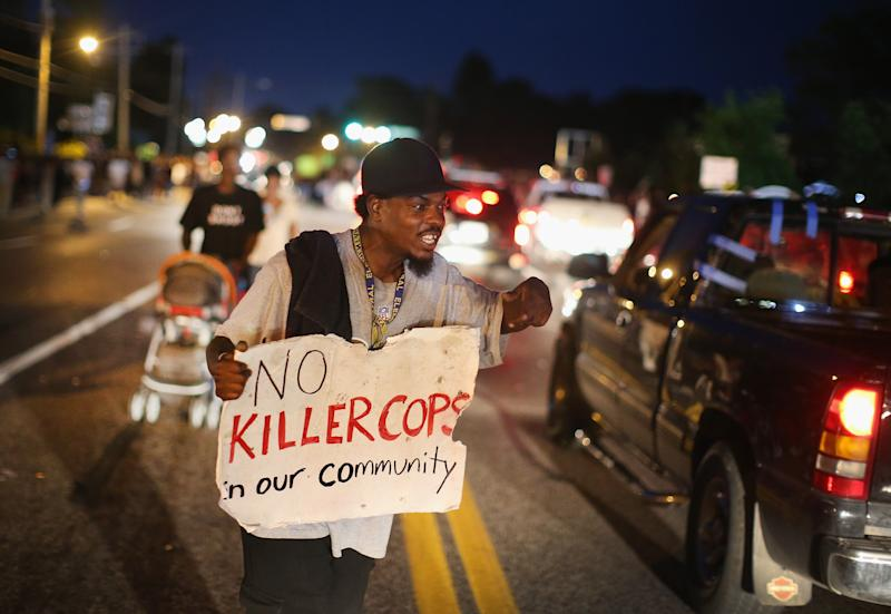 A demonstrator holds a sign along West Florissant Avenue to protest the shooting death of Michael Brown, in Ferguson, Missouri, on August 14, 2014