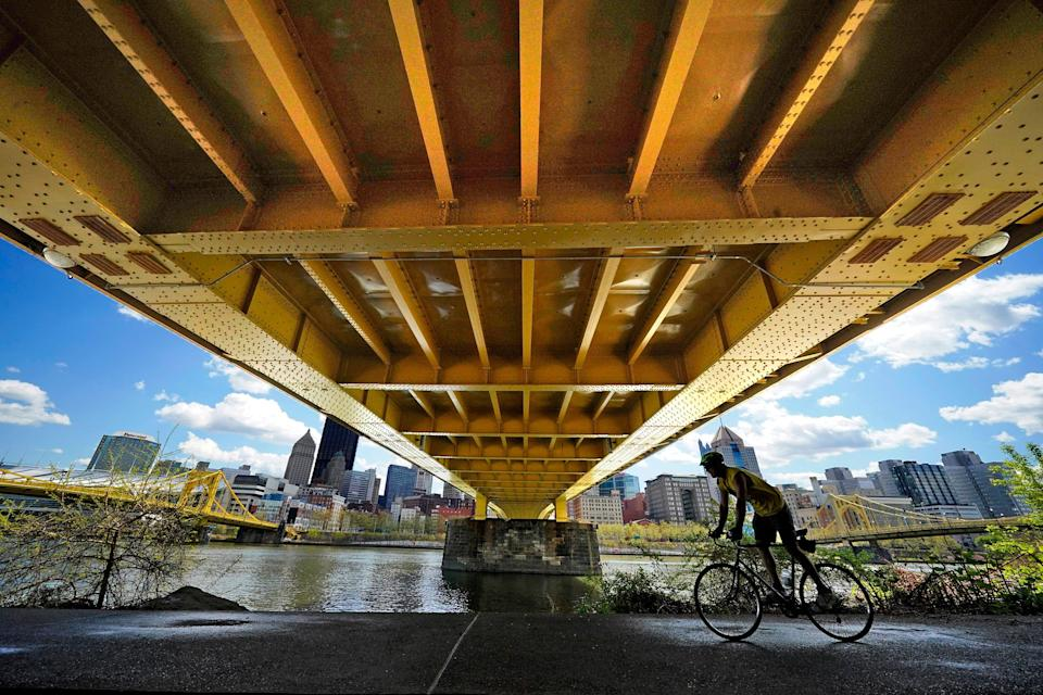 A cyclist rides on the North Shore Riverfront trail under the recently refurbished Andy Warhol bridge in downtown Pittsburgh, Monday, April 19, 2021.