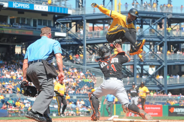 Andrew McCutchen takes a flying leap over catcher J.T. Realmuto to try and avoid a tag. (Getty Images)
