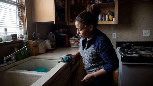 PHOTO: Maria Pineda cleans the kitchen of a home, where she temporarily stays, Feb. 18, 2021, in Conroe, Texas. (Gustavo Huerta/Houston Chronicle via AP)