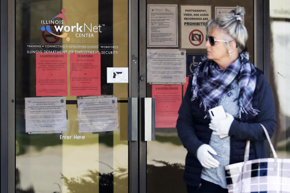 A woman looks to get information about job application in front of IDES (Illinois Department of Employment Security) WorkNet center in Arlington Heights, Ill., Thursday, April 9, 2020. Another 6.6 million people filed for unemployment benefits last week, according to the US Department of Labor, as American workers continue to suffer from devastating job losses, furloughs and reduced hours during the coronavirus pandemic. (AP Photo/Nam Y. Huh)