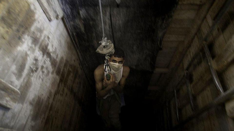 Palestinian man is lowered into a smuggling tunnel beneath the Gaza-Egypt border 4 June 2010