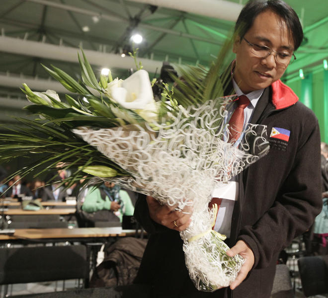 Naderev Sano from the Philippines holds flowers that where presented by other nations and organizations as a sympathy symbol for the Philippine people hit by typhoon Haiyan during the United Nations Climate Change Conference in Warsaw, Poland, Monday, Nov. 11, 2013. (AP Photo/Czarek Sokolowski)