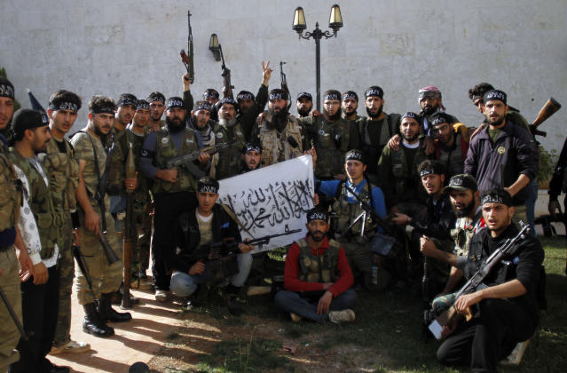 """In this Wednesday, Nov. 14, 2012 photo, Syrian commander, Mustafa Filfileh, top center, with fighters of """"The Beloved of Allah,"""" brigade pose for a photograph before fighting with government forces on the outskirts of Aleppo. The Beloved of Allah began with ten men, five rifles, one rickety machine gun and a few rocket-propelled grenades soon discovered to be duds. It was born in Maaret Misreen, a town where tractors nearly outnumber cars between the provincial capital of Idlib and the Turkish border to the north. Their leader, 35-year-old Mustafa Filfileh, had no military experience and little idea how to face one of the Mideast's strongest armies. He didn't even know how to drive. They learned fast. In November, the brigade called """"The Beloved of Allah"""" braced for its biggest challenge yet, one that would make clear how far its members had come and how far the war had brought them from their former lives. (AP Photo/ Khalil Hamra)"""