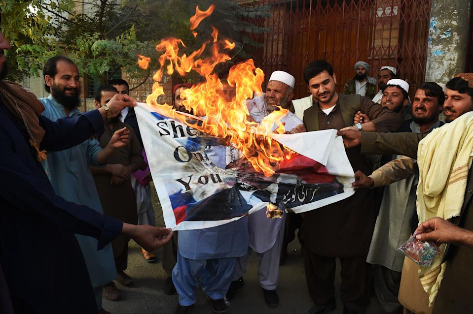 Demonstrators burn a poster with a picture of French President Emmanuel Macron with a footprint over his face during a protest following Macron's comments of Macron over Prophet Mohammed caricatures, in Quetta on October 26, 2020. - Pakistan on October 26 summoned French envoy to register protest over President Emmanuel Macron comments and for re-publishing of caricatures of Prophet Mohammed in a paris based magazine. (Photo by Banaras KHAN / AFP) (Photo by BANARAS KHAN/AFP via Getty Images)