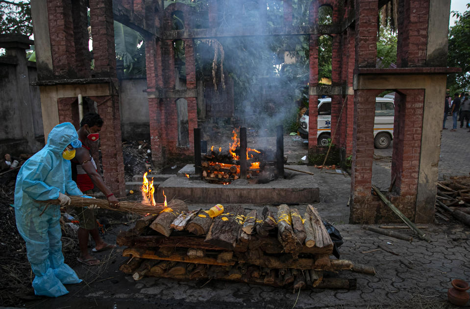 An Indian woman performs rituals near the body of her husband who died of COVID-19 in Gauhati, India, Monday, Sept. 28, 2020. India's confirmed coronavirus tally has reached 6 million cases, keeping the country second to the United States in number of reported cases since the pandemic began. (AP Photo/Anupam Nath)
