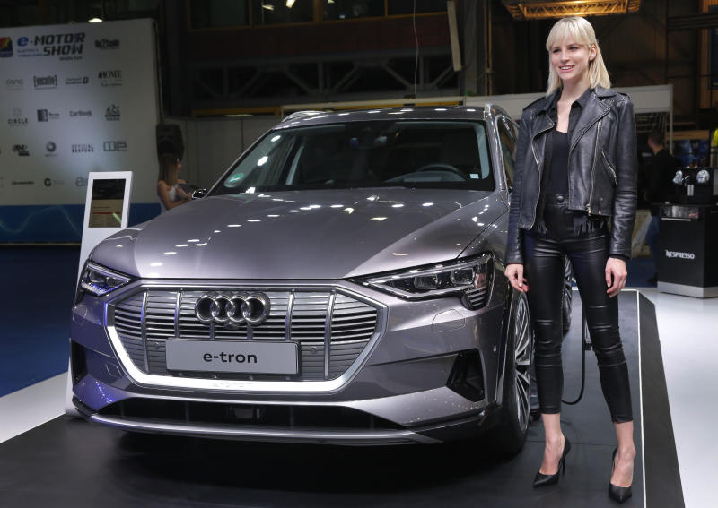 A model stands next of the new electric Audi e-tron Quatro, which display at the e-Motor show, in Beirut, Lebanon, Thursday, April 11, 2019. The e-Motor Show is the First auto show in the Middle East for electric and hybrid cars which opened its doors in Beirut for five days offering thousands of auto lovers the unique opportunity to be the first to see and test the recent releases of electrified cars that arrived to Lebanon by the top brands and to learn about these new technologies via daily Tech-Talk interactive sessions. (AP Photo/Hussein Malla)
