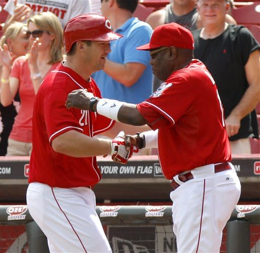 Cincinnati Reds' Scott Rolen, left, is congratulated by manager Dusty Baker, right, after Rolen hit a game winning sacrifice fly off Chicago Cubs relief pitcher Rafael Dolis during the 10th inning of a baseball game, Thursday, May 3, 2012, in Cincinnati. The Reds won 4-3. (AP Photo/David Kohl)