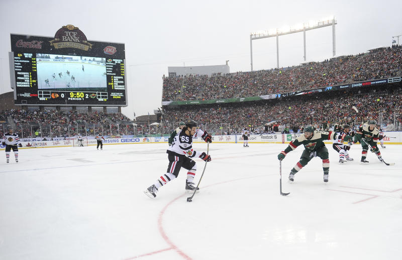 FILE - In this Feb. 21, 2016, file photo, Chicago Blackhawks center Andrew Shaw, left, take a shot on goal past Minnesota Wild center Mikko Koivu during the first period of the NHL Stadium Series hockey game at TCF Bank Stadium, in Minneapolis. The Minnesota Wild, after years of lobbying the league, will finally host the NHL's signature regular season event next year. The 2021 Winter Classic will coincide with the franchise's 20th anniversary season.(AP Photo/Craig Lassig, File)
