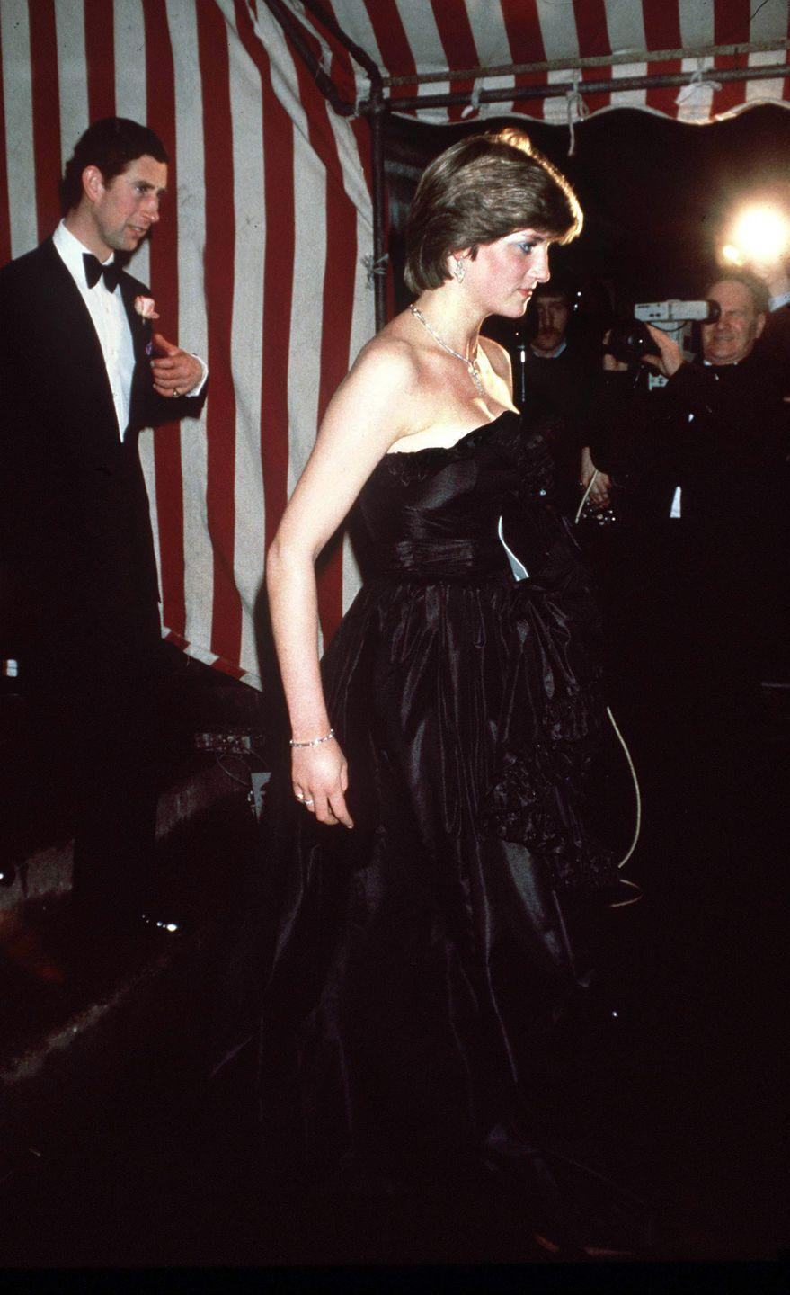 <p>In a black taffeta dress by the the Emanuels, with a diamond tennis bracelet and necklace, attending a fundraising concert at Goldsmiths Hall in London. </p>
