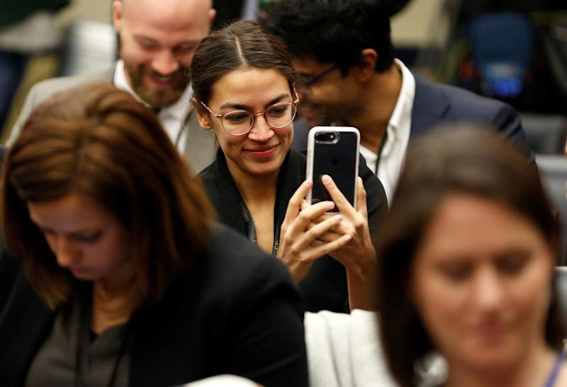 Alexandria Ocasio Cortez looks at her phone