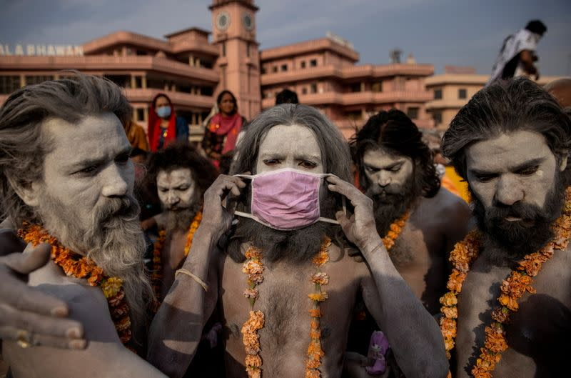"""FILE PHOTO: A Naga Sadhu, or Hindu holy man wears a mask before the procession for taking a dip in the Ganges river during Shahi Snan at """"Kumbh Mela"""", or the Pitcher Festival, amidst the spread of the coronavirus disease (COVID-19), in Haridwar"""