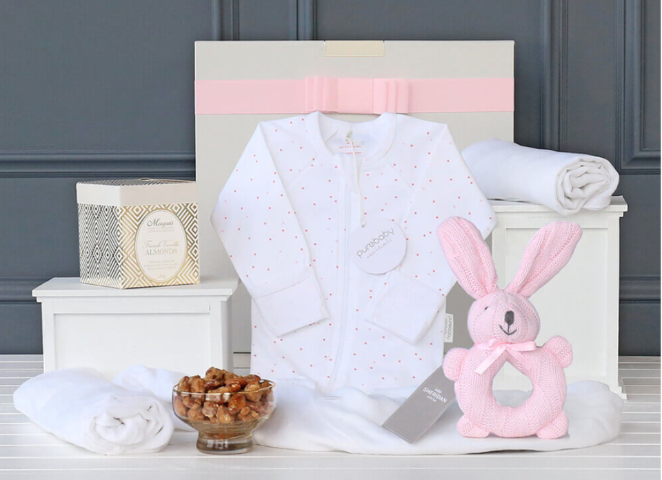 gift basket with Purebaby onesie, a soft rattle from Sheridan, muslin wrap and a little sweet treat for mum