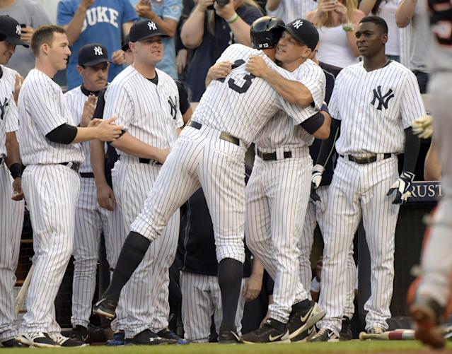 New York Yankees' Alex Rodriguez (13) hugs manager Joe Girardi after Rodriguez hit a home run during the first inning of a baseball game against the Detroit Tigers on Friday, June 19, 2015, at Yankee Stadium in New York. The home run was his 3,000 career hit. (AP Photo/Bill Kostroun)
