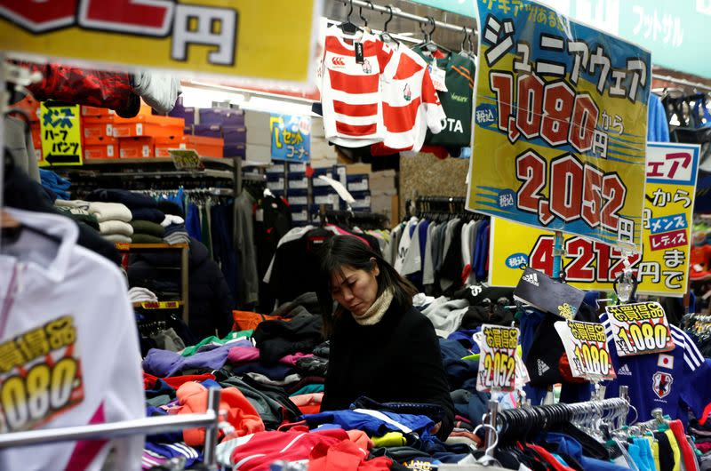 FILE PHOTO: A woman chooses clothes at a shop in Tokyo