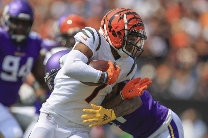 Cincinnati Bengals wide receiver Ja'Marr Chase (1) runs as Minnesota Vikings defensive back Bashaud Breeland tries to tackle him in the first half of an NFL football game, Sunday, Sept. 12, 2021, in Cincinnati. (AP Photo/Aaron Doster)
