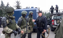 FILE - In this Aug. 23, 2020, file image made from video provided by the State TV and Radio Company of Belarus, Belarus President Alexander Lukashenko greets riot police officers near the Palace of Independence in Minsk, Belarus, amid street protests. Political prisoners in Belarus are coming under increasing pressure following the recent arrest of activist Raman Pratasevich from a forcibly diverted Ryanair flight. Human rights groups say these prisoners have been marked with yellow tags sewn into their prison uniforms to single them out from regular prisoners. (State TV and Radio Company of Belarus via AP, File)