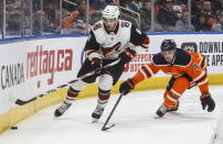Arizona Coyotes' Nick Schmaltz (8) is chased by Edmonton Oilers' Kris Russell (4) during third period NHL action in Edmonton, Alberta, on Saturday, Jan. 18, 2020. (Jason Franson/The Canadian Press via AP)
