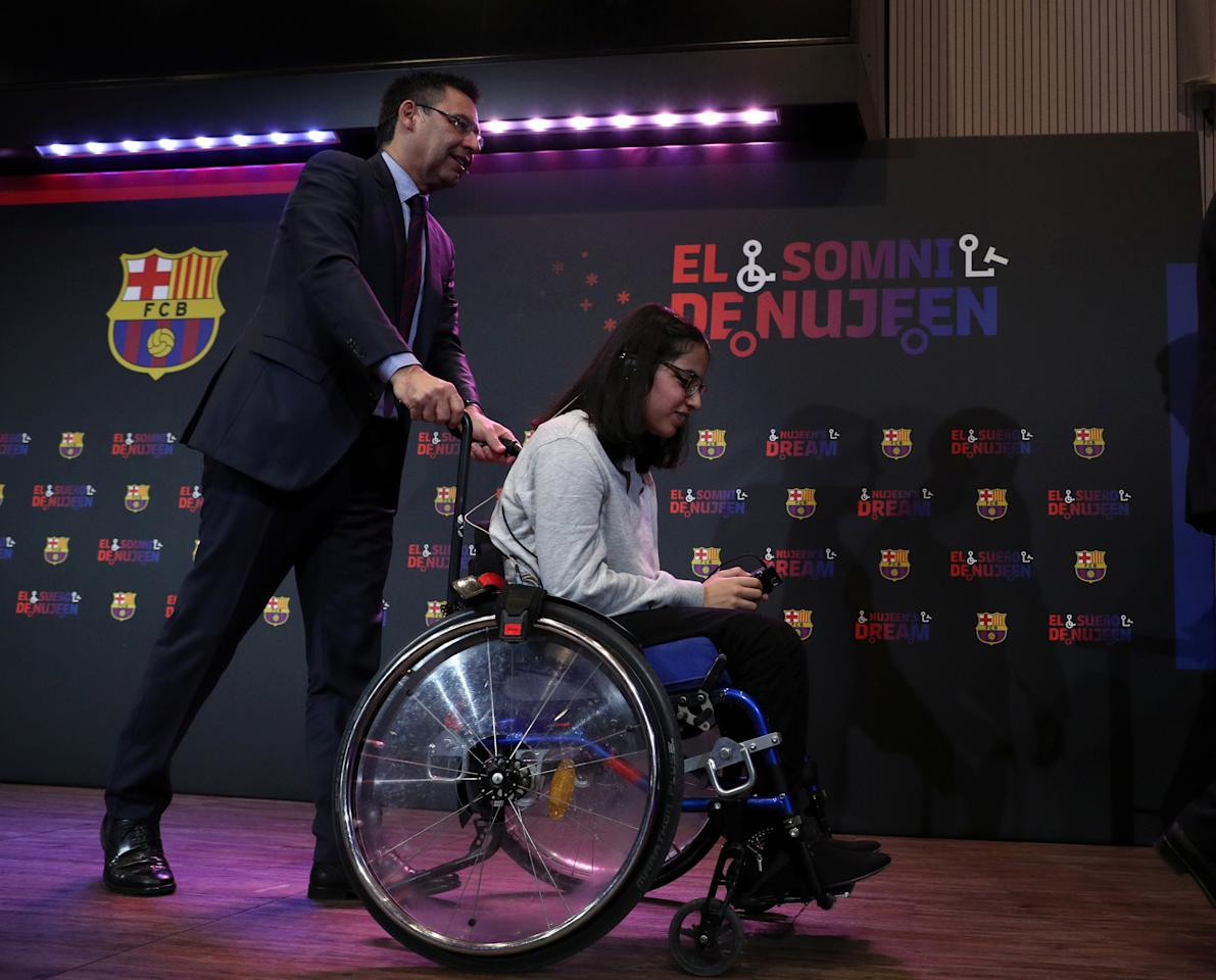 """Barcelona's President Josep Maria Bartomeu pushes wheelchair of Syrian refugee Nujeen Mustafa during a charity Christmas event """"Nujeen's dream"""" at Camp Nou stadium in Barcelona, Spain, December 14, 2017.  REUTERS/Albert Gea"""