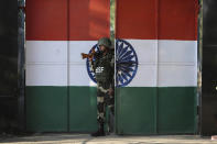 FILE - In this Jan. 23, 2020, file photo, an Indian Border Security Force soldier walks through a gate painted with the Indian flag at the India-Pakistan border at Suchet Garh in Ranbir Singh Pura, about 27 kilometers (17 miles) south of Jammu, India. The Line of Control, a highly militarized de facto border that divides the disputed region between the two nuclear-armed rivals India and Pakistan, and a site of hundreds of deaths, is unusually quiet after the two South Asian neighbors agreed in February, 2021, to reaffirm their 2003 cease-fire accord. (AP Photo/Channi Anand, File)