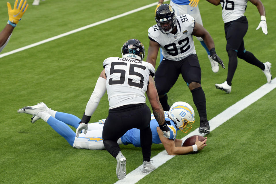 Los Angeles Chargers quarterback Justin Herbert, bottom, lunges into the end zone for a touchdown during the second half of an NFL football game against the Jacksonville Jaguars Sunday, Oct. 25, 2020, in Inglewood, Calif. (AP Photo/Kyusung Gong)