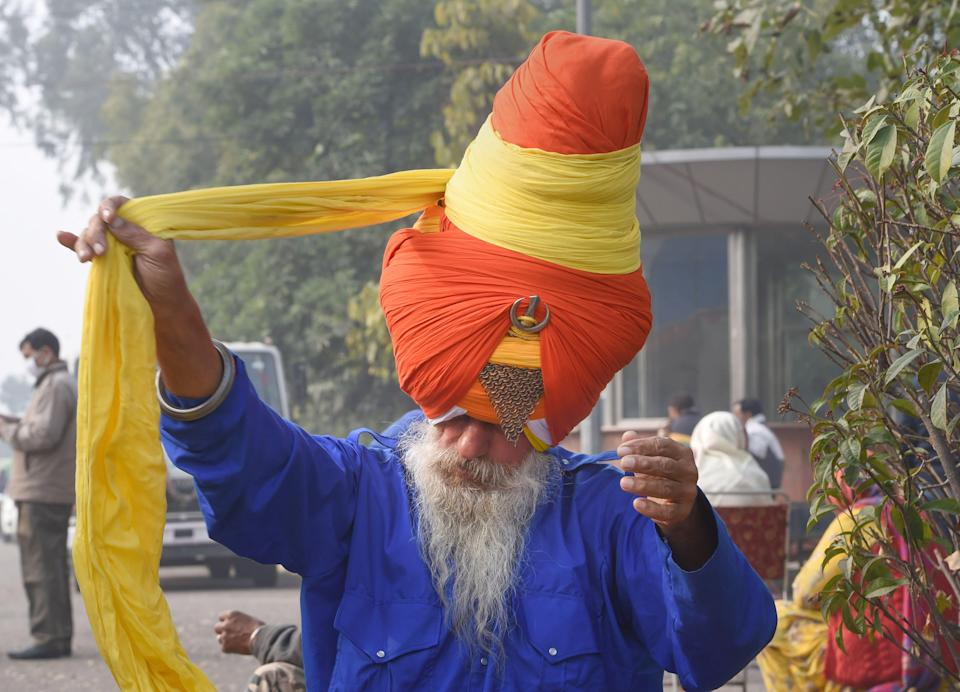 A 'Nihang' or Sikh religious warrior ties his turban during the ongoing farmers' agitation over the new farm laws, in New Delhi, on Sunday, 17 January 2021.