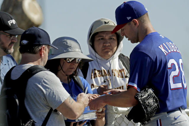Texas Rangers pitcher Corey Kluber, right, gives autographs during spring training baseball practice Friday, Feb. 14, 2020, in Surprise, Ariz. (AP Photo/Charlie Riedel)