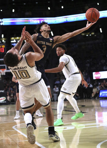 Notre Dame guard Prentiss Hubb knocks Georgia Tech guard Jose Alvarado to the hardwood on his way to the basket in the final minutes of an NCAA college basketball game Wednesday, Jan. 15, 2020, in Atlanta. (Curtis Compton/Atlanta Journal-Constitution via AP)