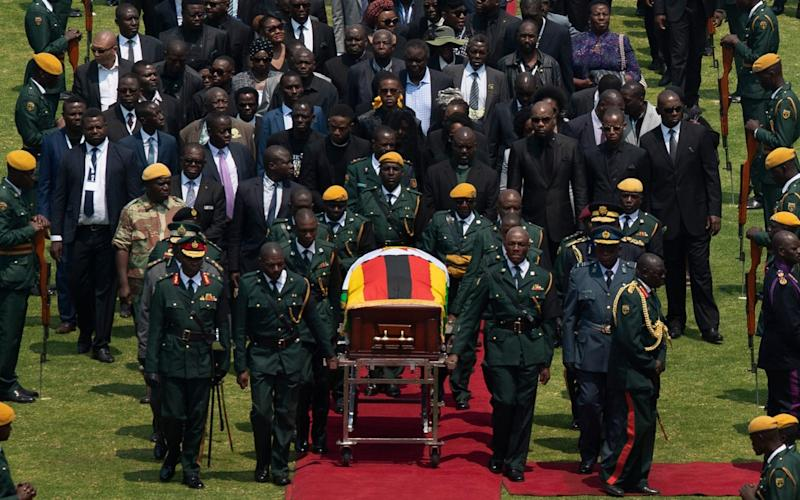 Robert Mugabe's coffin arrives for a state funeral at Harare's national stadium - AP