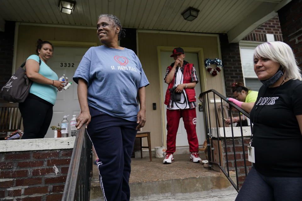 Lynda Brooks stands with others on the porch of an addiction recovery house in St. Louis on Wednesday, May 19, 2021. Brooks, a 55-year-old grandmother, had been addicted to crack for decades. She was often homeless and life out there was hard. She was assaulted, spit on, her husband died. So she took more drugs to escape feeling sad or scared or worthless. (AP Photo/Brynn Anderson)