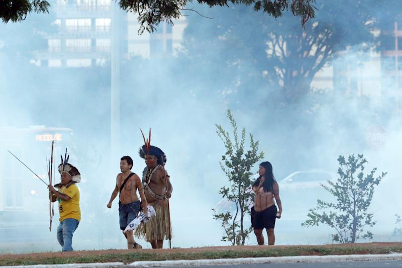 Protesters in traditional headdress points his bow and arrow towards the police