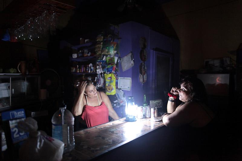 Flor Dalisa Contreras, left, talks with Virginia Rivas at a coffee shop during a power outage in San Juan, Puerto Rico, last week. (Alvin Baez / Reuters)