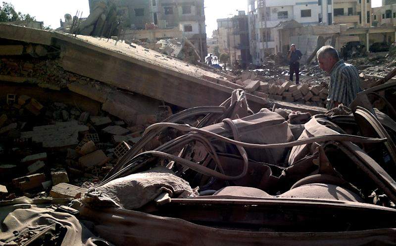In this photo released by the Syrian official news agency SANA, Syrian men inspect the scene of a car bomb attack in Qamishli, 497 miles (800 Kilometers) northeast Damascus, Syria, Sunday, Sept. 30, 2012. A suicide attacker detonates a car bomb at a Syrian security compound in a remote, predominantly Kurdish area, killing at least four people in the latest sign that Syria's largest ethnic minority is increasingly being drawn into a widening civil war.  (AP Photo/SANA)