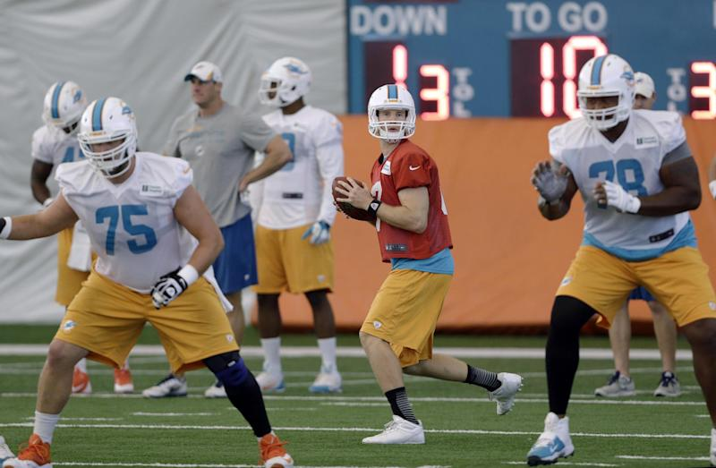 Miami Dolphins quarterback Ryan Tannehill, center, prepares to pass during NFL football practice, Wednesday, Nov. 6, 2013, in Davie, Fla. At left is guard Nate Garner (75) and at right is tackle Bryant McKinnie (78). A senior partner in a New York law firm with experience in sports cases has been appointed by NFL Commissioner Roger Goodell to investigate possible misconduct in the Dolphins' workplace and prepare a report. The Dolphins have pledged full support in the investigation, the NFL said. A troubled relationship between linemen Jonathan Martin and Richie Incognito left both players sidelined. (AP Photo/Lynne Sladky)