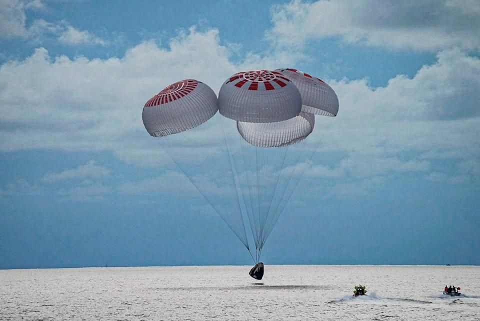 In this image taken provided by SpaceX, a capsule carrying four people parachutes into the Atlantic Ocean off the Florida coast, Saturday, Sept. 18, 2021. The all-amateur crew was the first to circle the world without a professional astronaut.