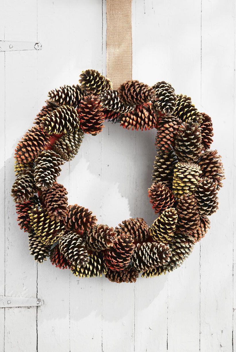 """<p>When it comes to fall crafts, there's nothing easier than a <a href=""""https://www.countryliving.com/diy-crafts/how-to/g312/all-about-pinecones-1206/"""" rel=""""nofollow noopener"""" target=""""_blank"""" data-ylk=""""slk:pine cone crafting project"""" class=""""link rapid-noclick-resp"""">pine cone crafting project</a>. These autumnal beauties are available right in your own backyard, and they're super easy to work with.<strong><br></strong></p><p><strong>Make the wreath:</strong> Wrap a 16-inch wreath form with burlap ribbon and loop a piece around the wreath form for hanging. Paint the tip of 40 pine cones in fall colors such as orange, yellow, and beige with acrylic paint. Brush the tips of 10 pine cones with matte Mod Podge and sprinkle with gold and copper glitter. once dry, wrap an 18-inch length of floral wire around the base of each pine cone and twist tie around the wreath form to secure, layering and overlapping them as you go. </p>"""