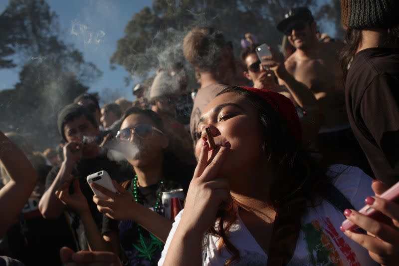 People smoke marijuana joints at 4:20 p.m. as thousands of marijuana advocates gather in Golden Gate Park in San Francisco, California