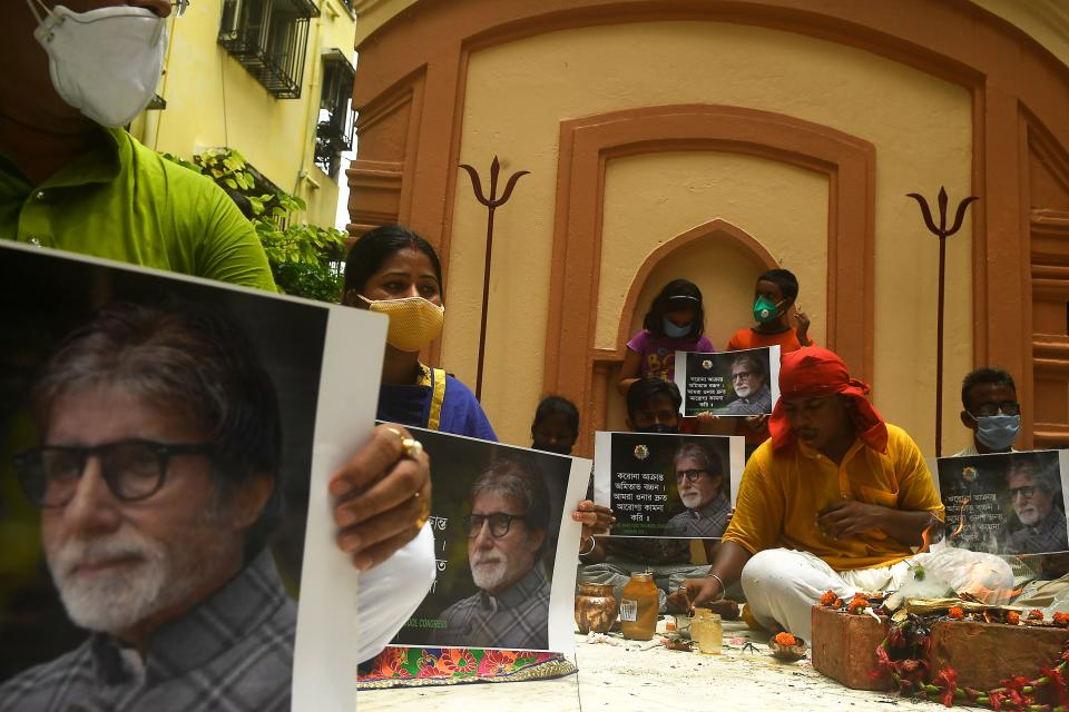 Fans of Bollywood actor Amitabh Bachchan hold posters of the actor while a priest (R) performs special rituals and prayers for his recovery as he tested positive for COVID-19, at a temple in Kolkata on July 12, 2020. - Bollywood megastar Amitabh Bachchan, 77, tested positive for COVID-19 on July 11 and was admitted to hospital in Mumbai, with his actor son Abhishek -- who also announced he had the virus -- saying both cases were mild. (Photo by Dibyangshu SARKAR / AFP)