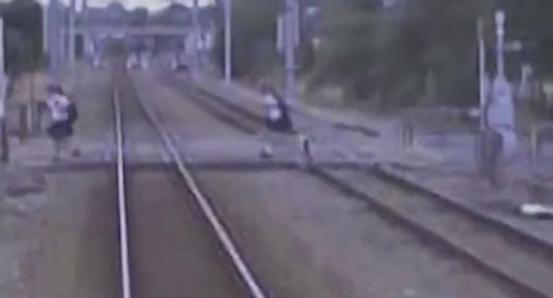 Two New Zealand school kids run over a crossing despite a train coming towards them.