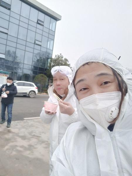 Wuhan resident Chen Hui poses for a selfie in protective suit with another volunteer as they deliver meat and vegetables to construction workers building a temporary hospital in Ezhou