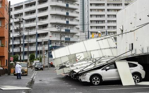<span>A temporary fence lies fallen on parked vehicles in Kawasaki, Kanagawa Prefecture</span> <span>Credit: Bloomberg </span>